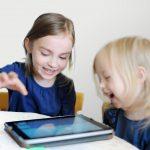 Twee kinderen lachend met een tablet