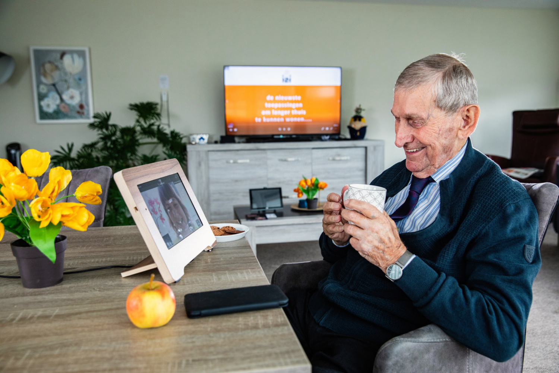 Lachende oude man die aan het videochatten is
